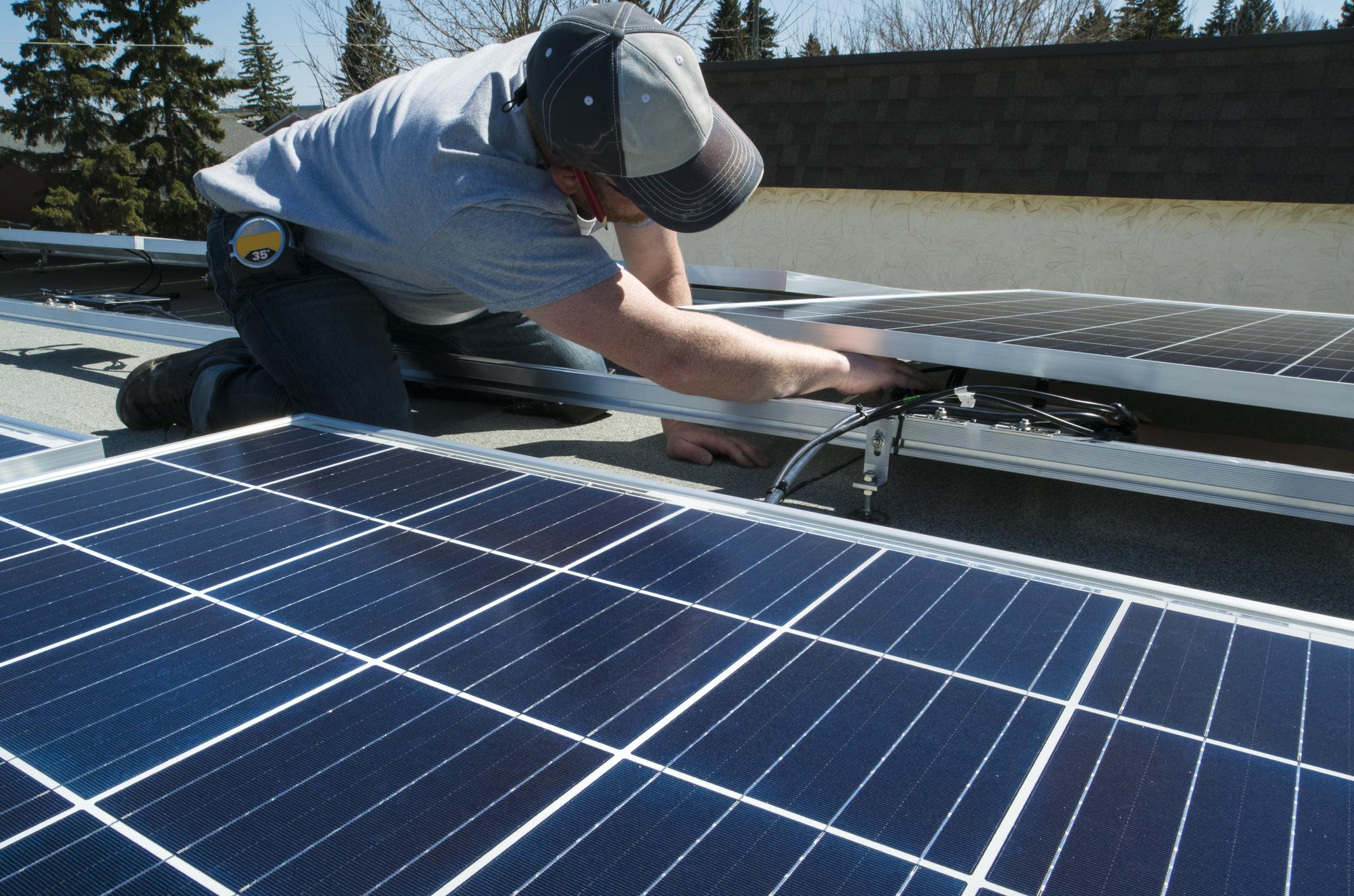 Werknemer zonnepanelen op plat dak installeert Energreen