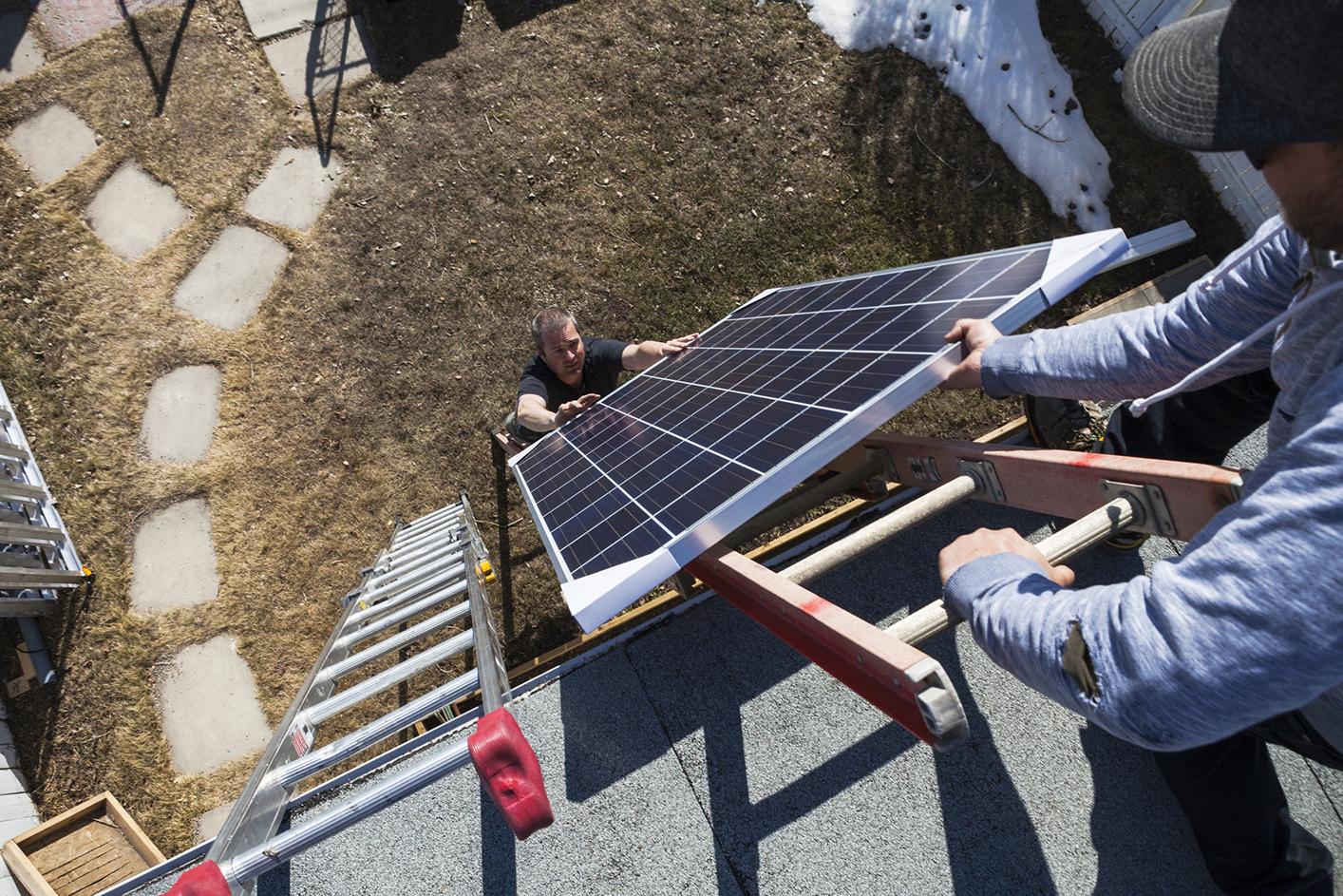 Ouvrier pose de panneaux solaires photovoltaïques sur toit incliné Energreen