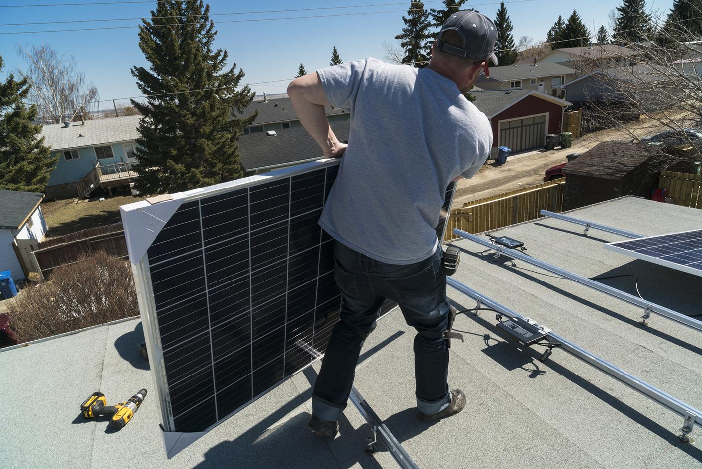 Ouvrier pose de panneaux solaires photovoltaïques sur toit plat Energreen