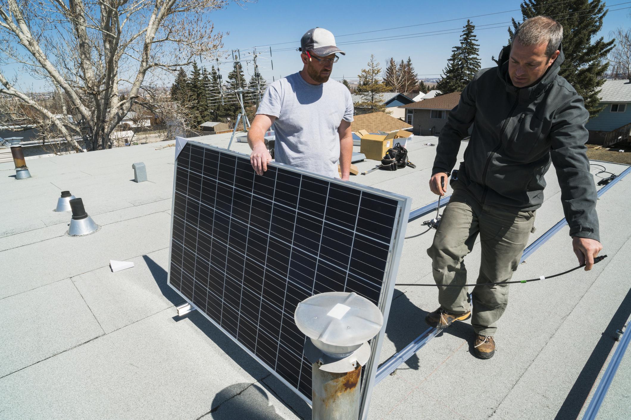 Ouvrier technicien pose de panneaux solaires photovoltaïques sur toit plat Energreen